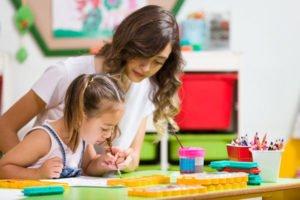 Pre-Kindergarten Girl and Teacher Painting in Classroom