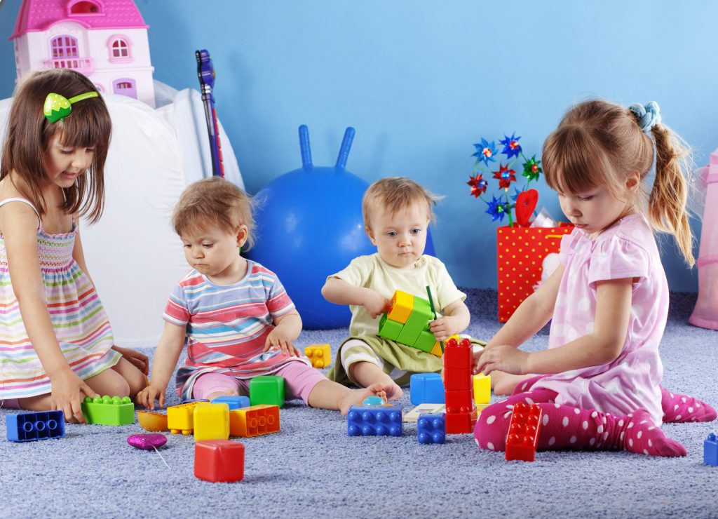 4 children playing blocks at a daycare