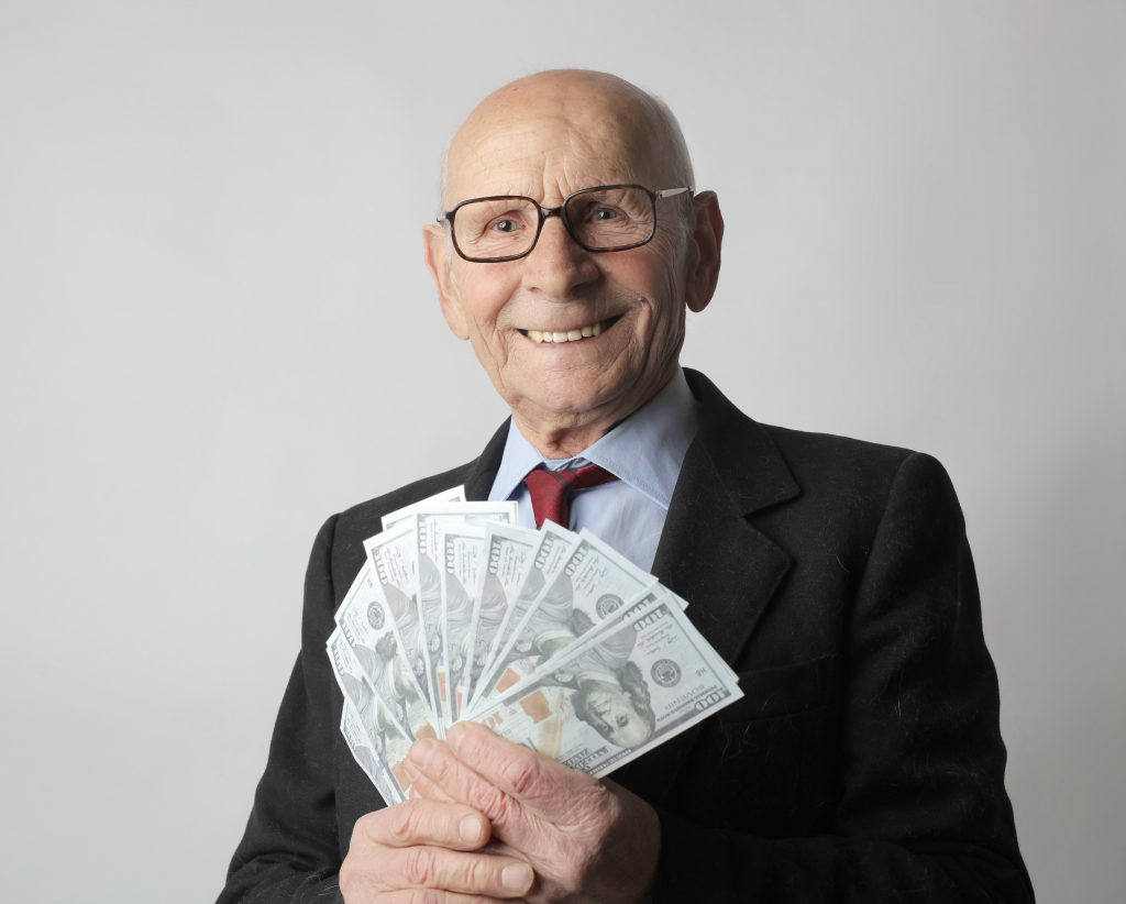 happy older man with money fanned out