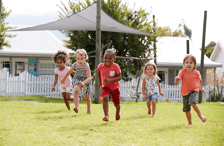Children in the backyard running at a daycare